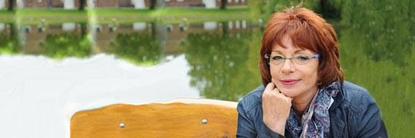 Thoughtful woman with red hair and glasses resting her hand on her chin on park bench with pond and reflected trees in the background.