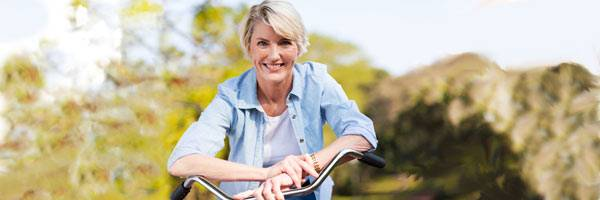 Woman in denim shirt resting her forearms on bicycle handlebar with trees and mountains in the background.