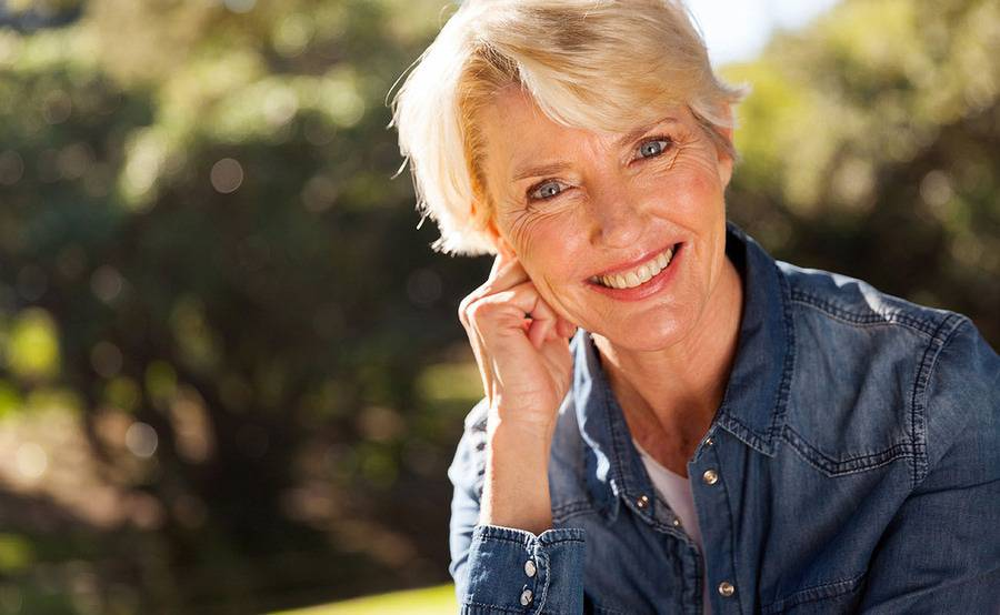 A smiling middle-aged woman represents a healthier life with treatment for venous disease or varicose veins.