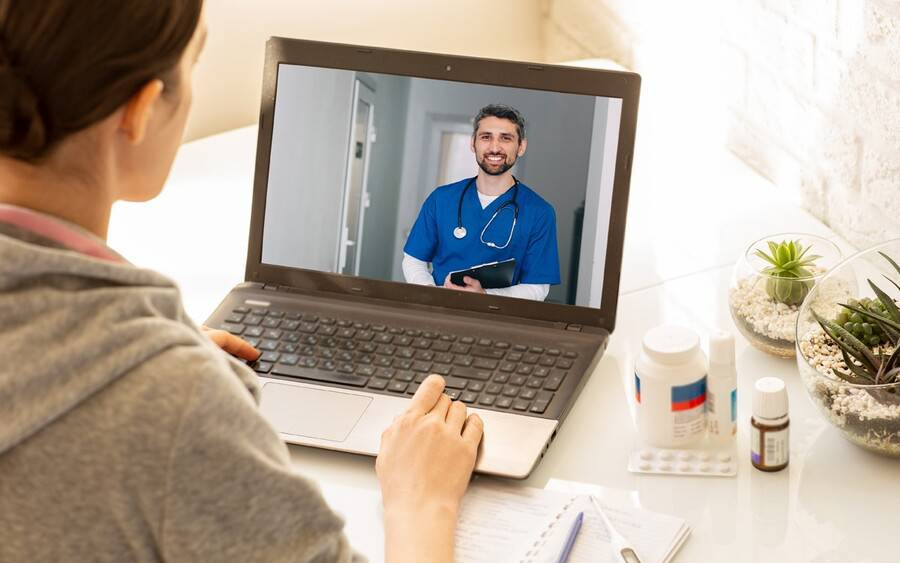 Doctor conducts medical appointment using video conferencing.
