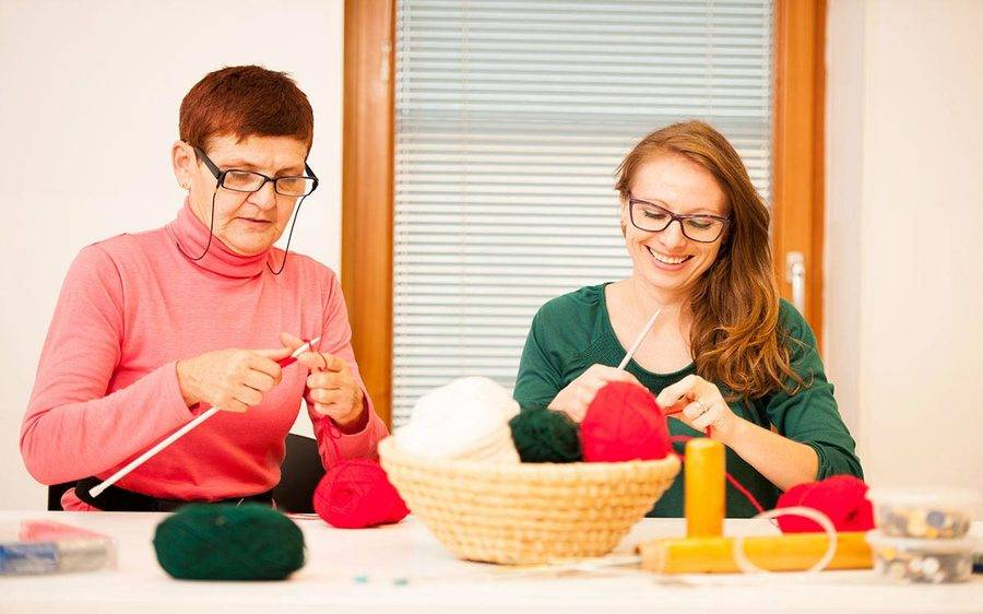 Mature and yound woman in knitting class