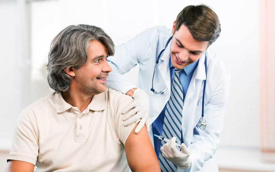 A cheerful male patient confers with his physician while receiving a flu vaccination.