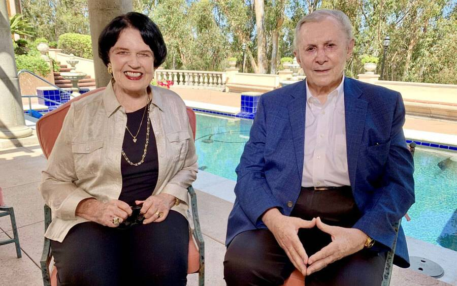 (From left) Debbie and Warner Lusardi sit near a sparkling pool and are happy about their recent $25 million gift to Scripps.