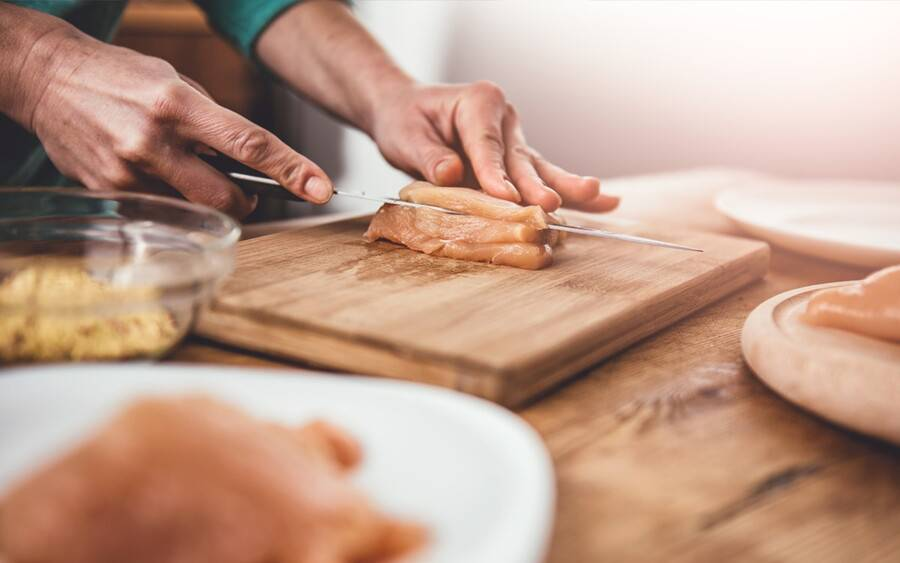 A cook prepares chicken meat on a board separate from other ingredients to prevent potential food poisoning.