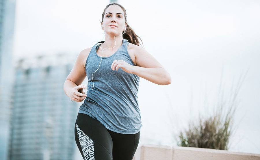 A woman running while wearing headphones, representing the active lifestyle people often enjoy following medically supervised weight management at Scripps.