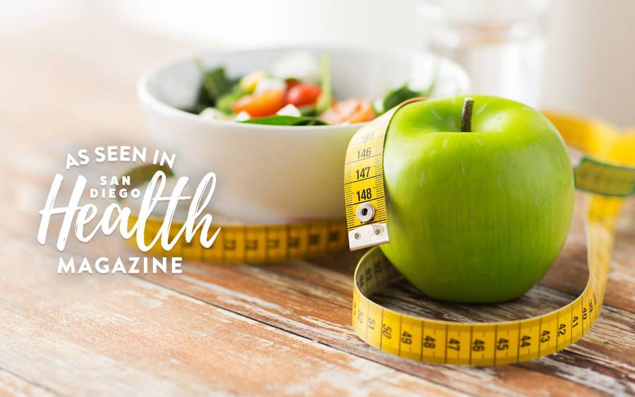 A healthy bowl of veggies, an apple and a measuring tape are featured in article about weight loss strategies.