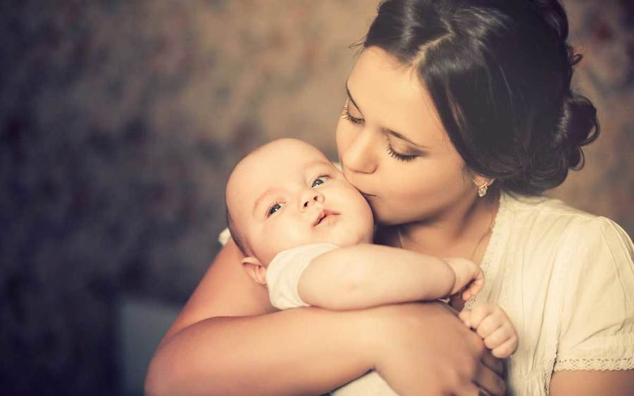 A mother kisses her infant in a quiet indoor setting
