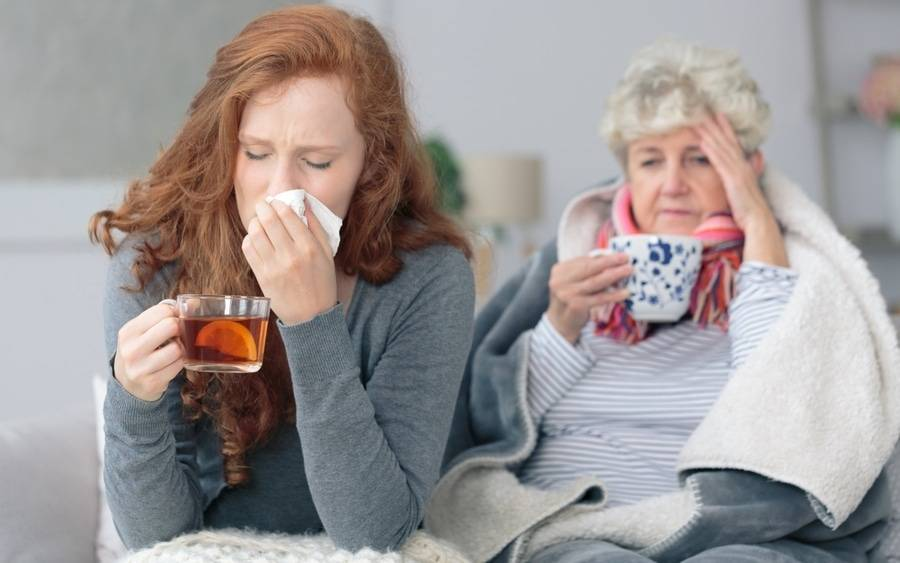 A mother and daughter fight cold and flu symptoms with hot tea and rest.