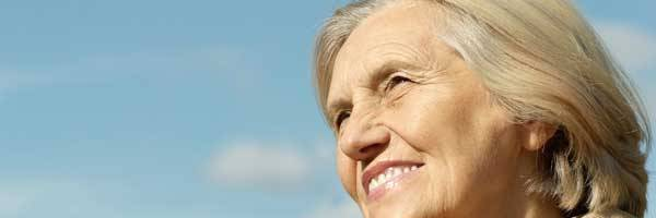 Thoughtful woman in her fifties smiling with blue skies and white clouds in the background.