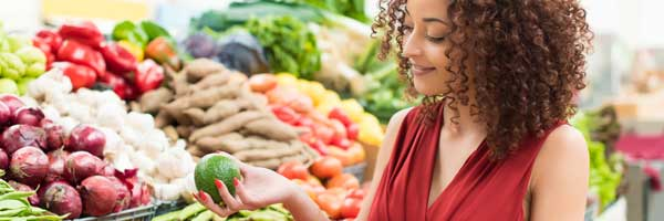 Woman shopping for healthy fruits and vegetables at the grocery store.