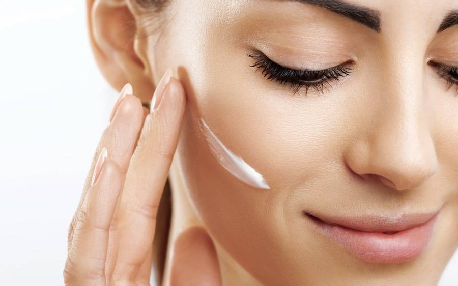 Woman with healthy skin applying moisturizer.