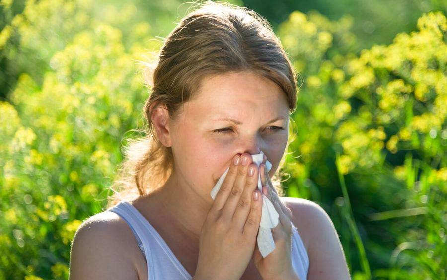 Woman sneezes due to allergies.
