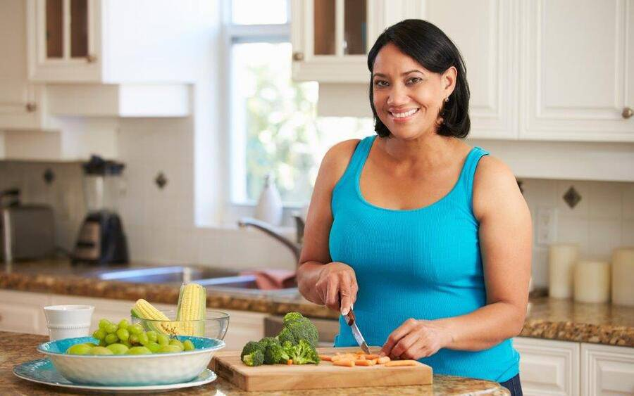 A woman making a healthy meal in her kitchen.