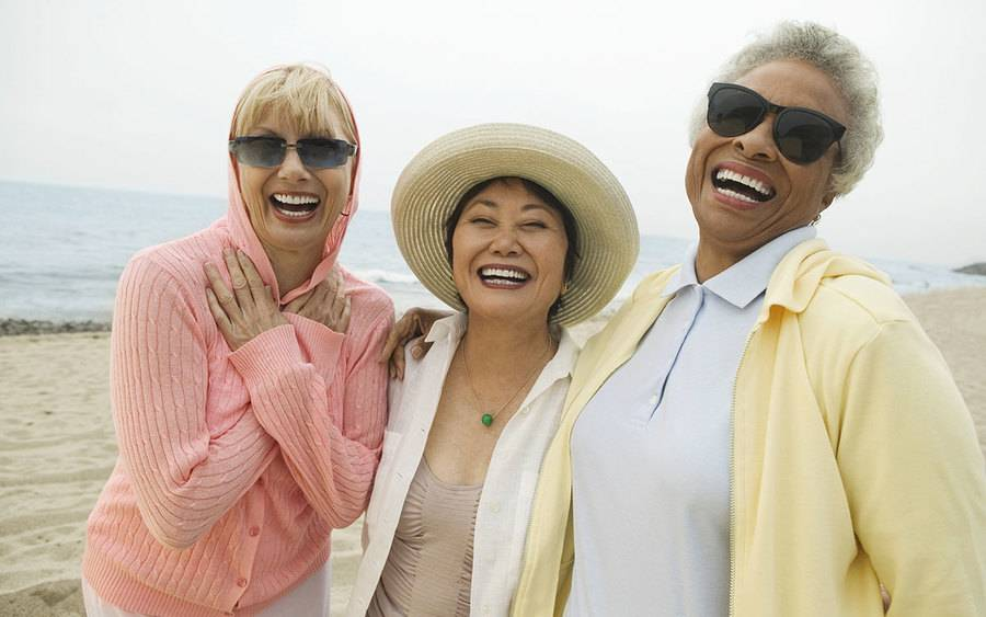 3 diverse mature women laughing on the beach