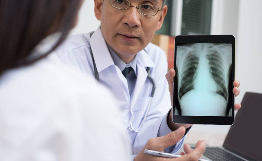 A doctor and patient look at a tablet device, representing the high-tech X-ray technology used at Scripps.