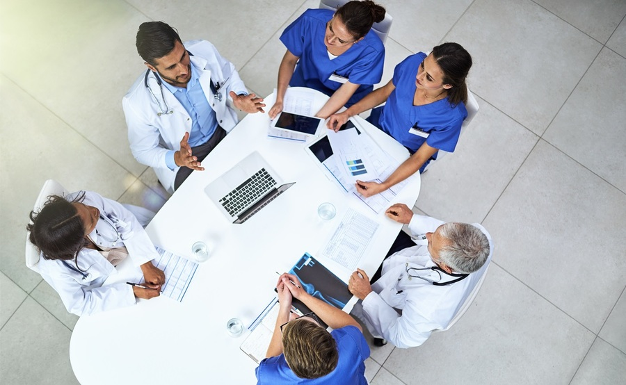 An aerial view of physicians in discussion around a table represents the evidence-based environment of the Scripps Clinic Internal Medicine Residency Program.