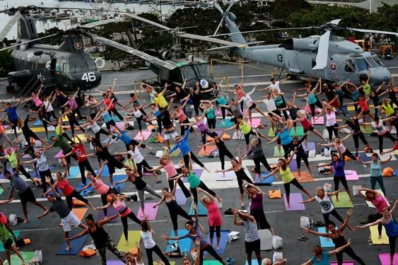 A group practicing yoga on the deck of an aircraft carrier in San Diego Harbor.