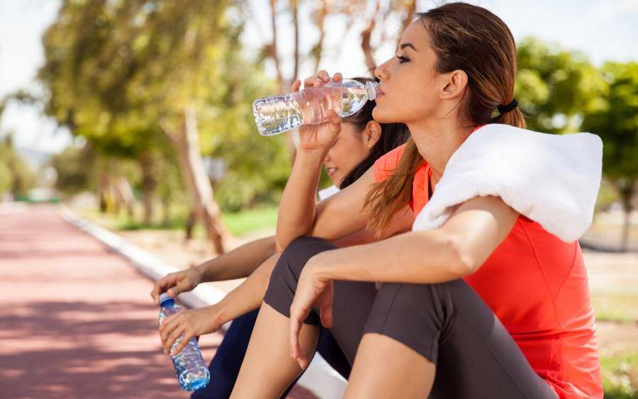 Two women resting and drinking water after a workout on a hot summer day.
