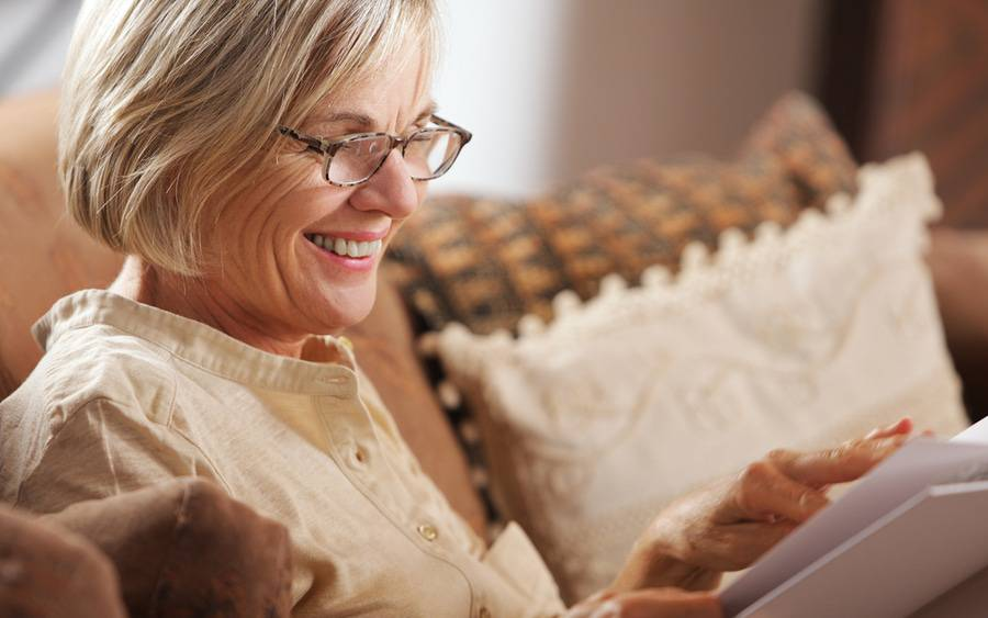 Older woman with presbyopia wears reading glasses to correct her poor vision.